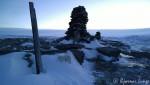 Trimvarden med en postkasse som nesten er forsvunnet i snøen