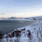 Mot bygda og sola skinner på fjellene på andre sia av fjorden